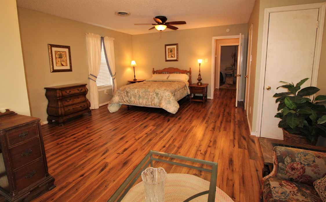 Lake Whitney, Texas vacation home rental | Lake Whitney Log Cabin wood floors in rustic master bedroom