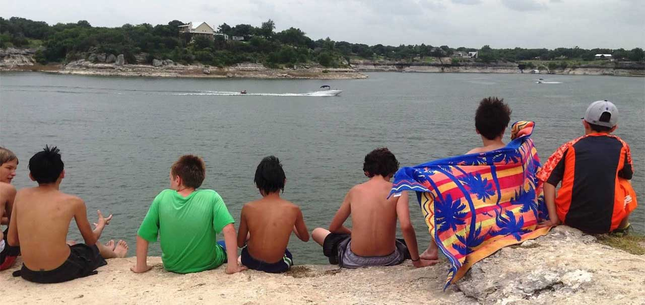 People watching boats drive by on the cliffs of Lake Whitney State Park